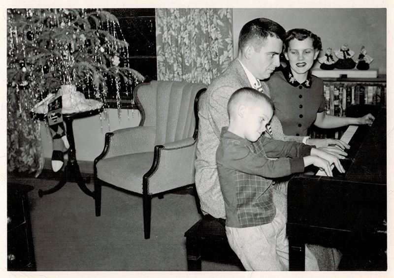 The Collins family playing piano with a small Christmas tree in the background