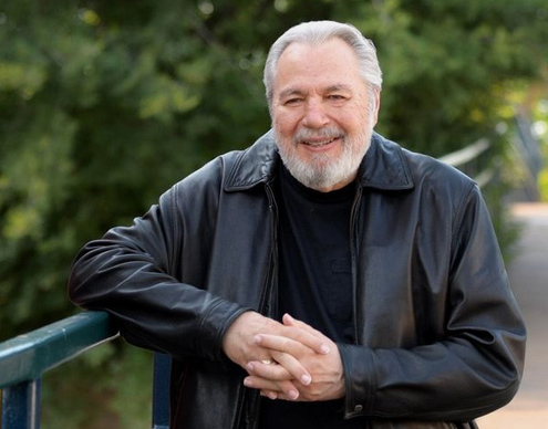 outdoor portrait of author John Lutz wearing a black shirt and jacket.