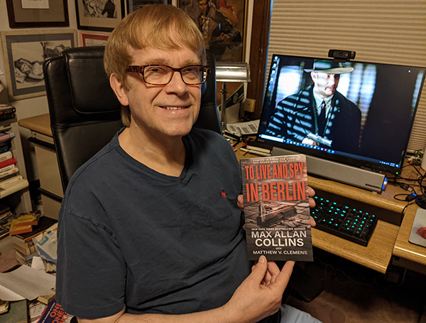 M.A.C. holding a copy of To Live and Spy in Berlin at his desk